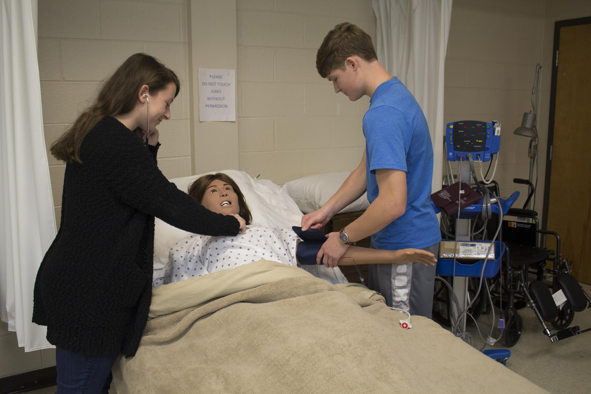 Two students take blood pressure of a mannequin