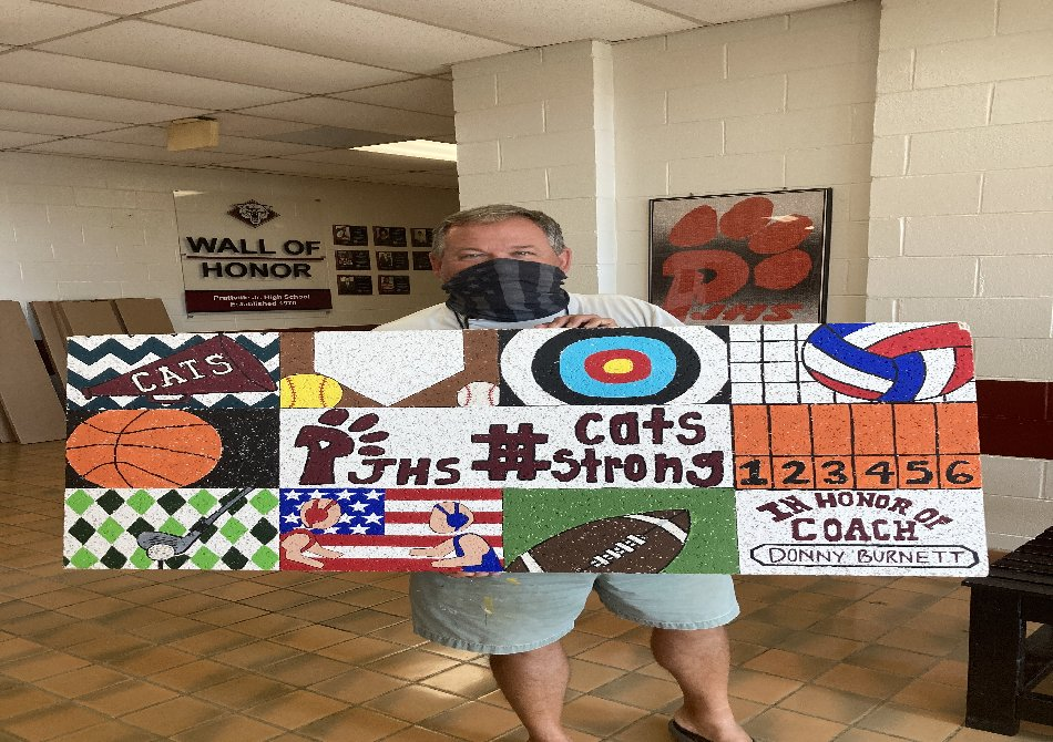 Coach Burnett holding sports themed ceiling tile created in his honor.