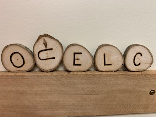 OCELC letters burned on slices of wood