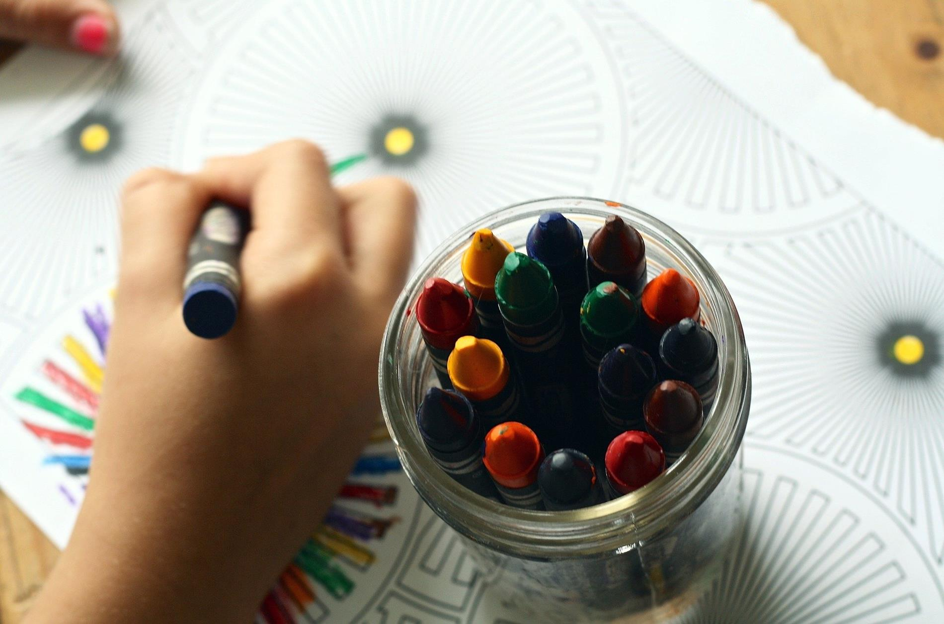 child's hand coloring a page beside a container of crayons