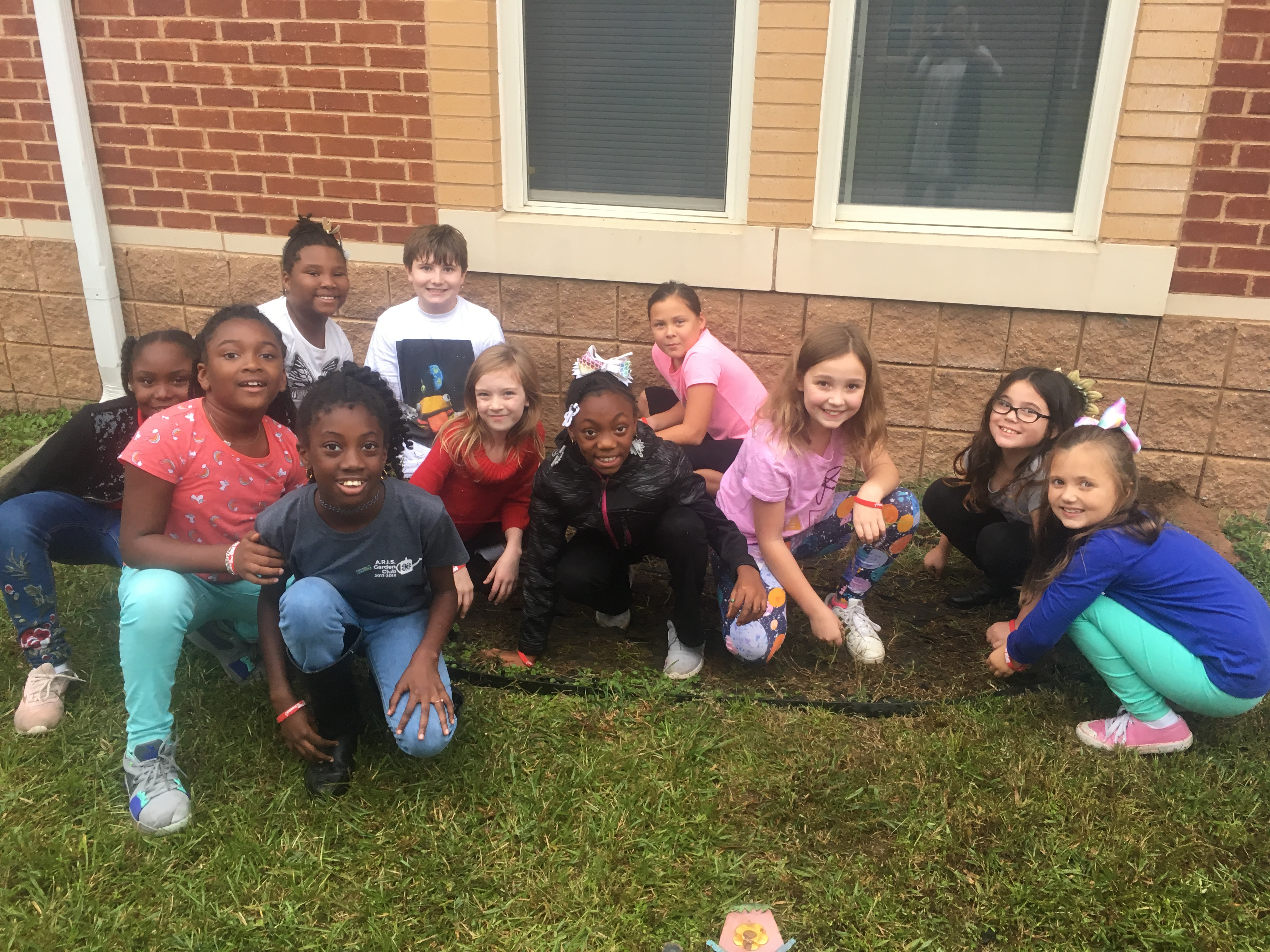 Students posing in flower bed
