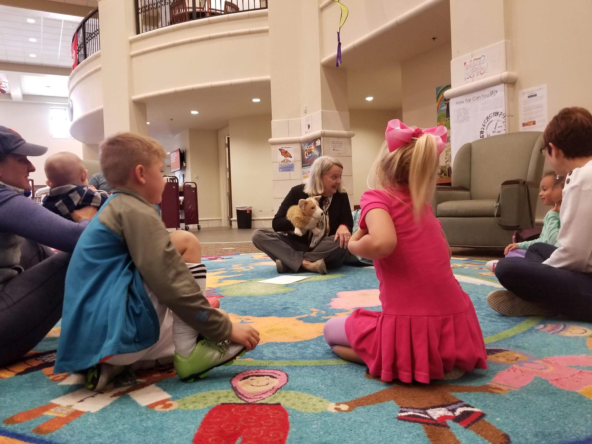 Children gathered around Mrs. Mary as she tells a story with her Corgi dog puppet, Cupcake