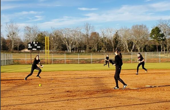 PJHS softball practicing with a ground ball to third base