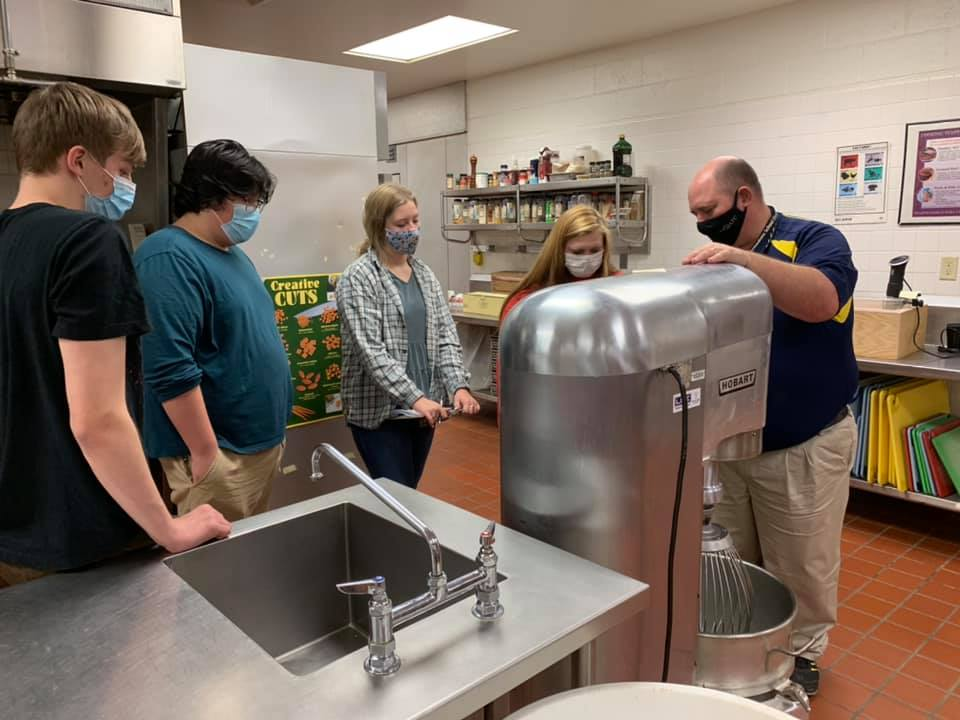 Students learning to use industrial sized equipment in the kitchen.