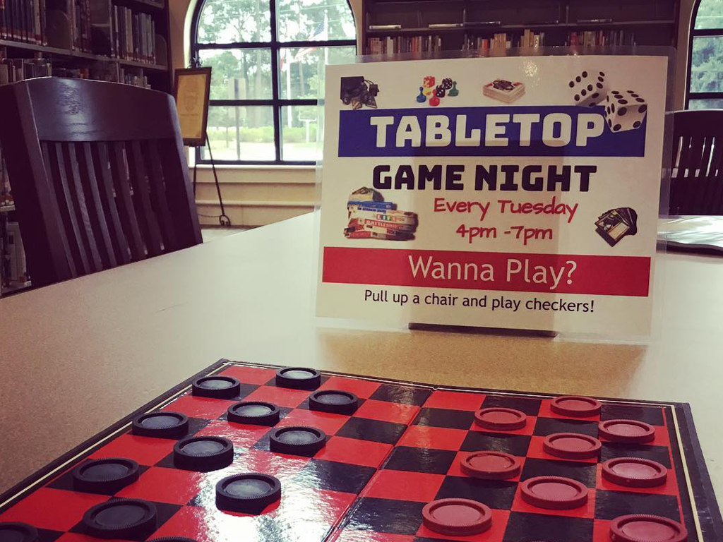 "Checkboard set up on a table at Spanish Fort Public Library. Sign on table reads, ""Tabletop Game Night, every Tuesday, 4pm - 7pm. Wanna Play? Pull up a chair and play checkers!"""