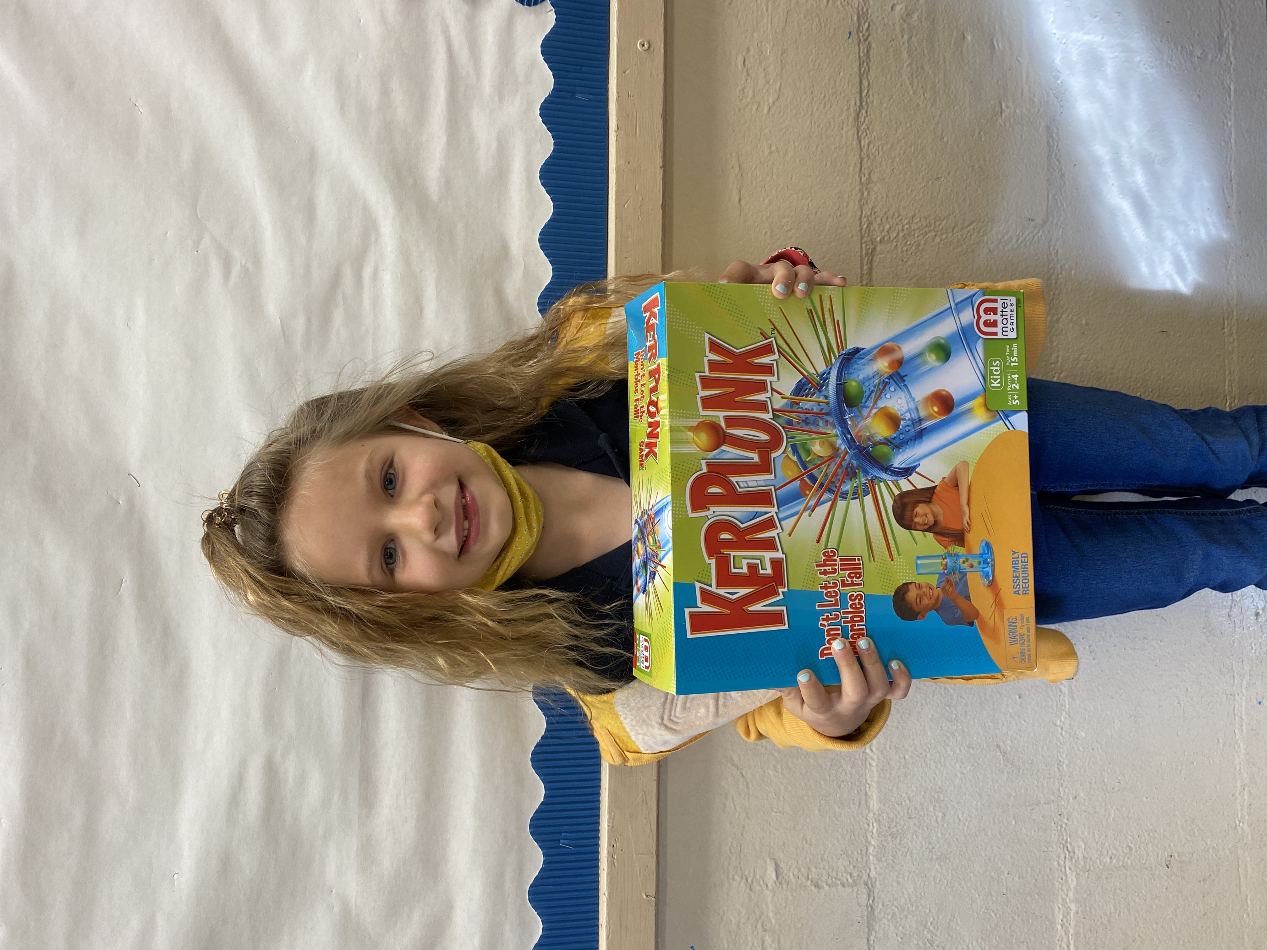 A student holding their Kerplunk Game they won.