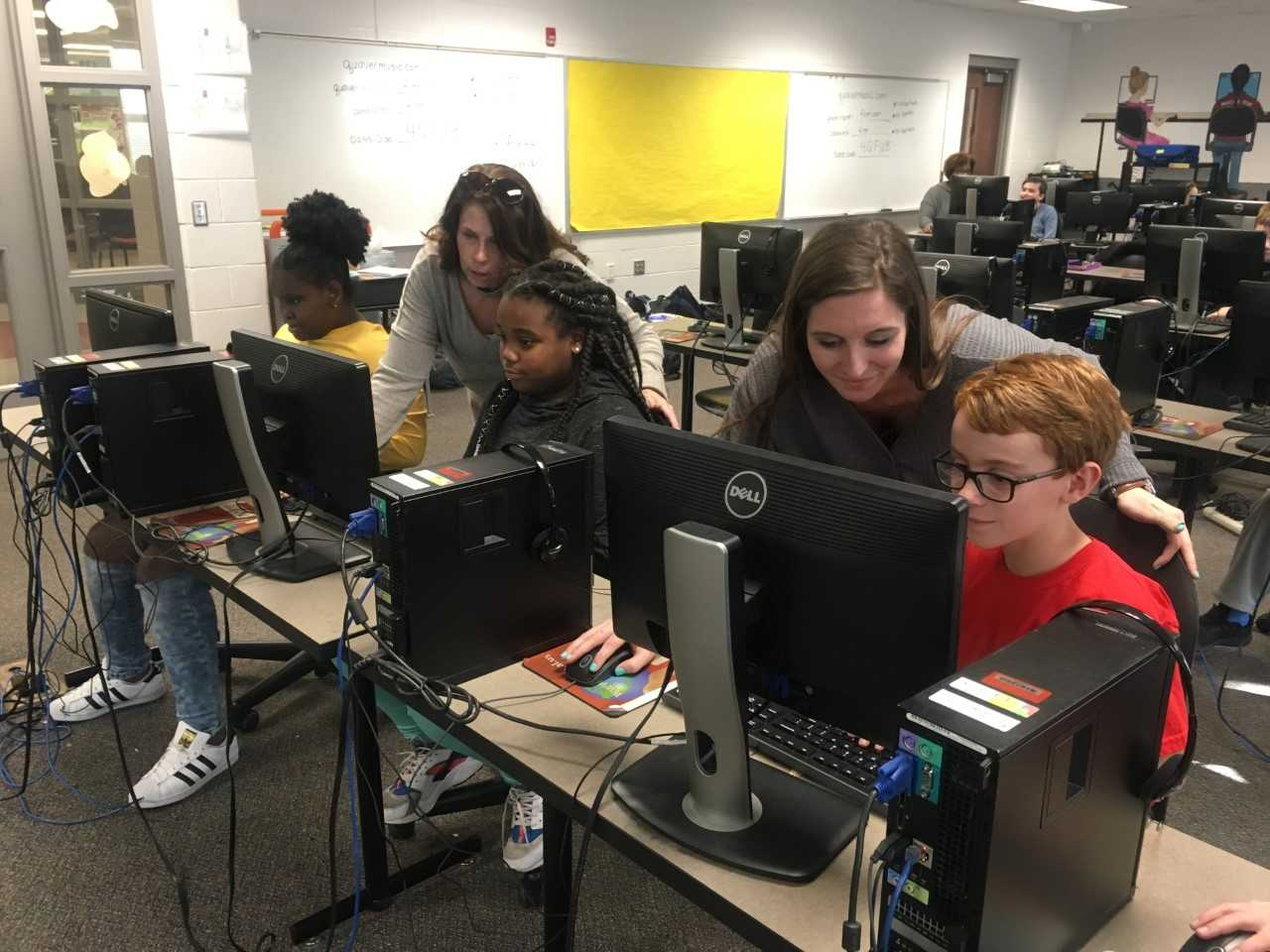 Teachers helping students on computers