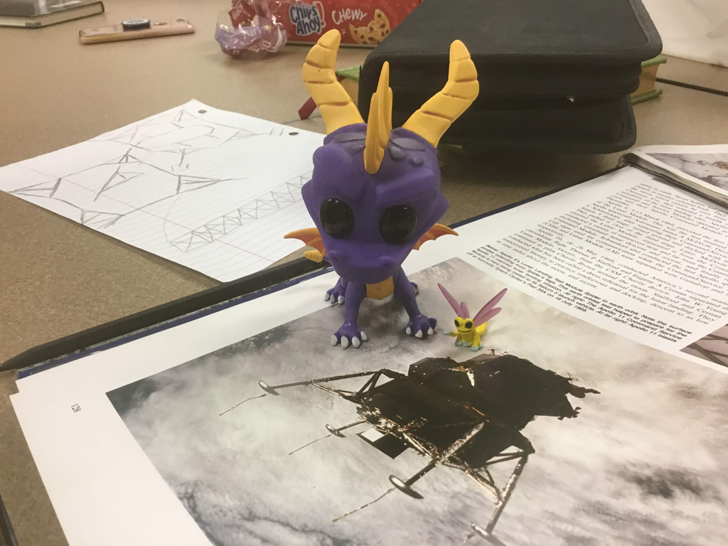 Vinyl pop dragon figure with tiny bug toy figure on top of open book of NASA photos of the Apollo 11 Eagle lander in space with a pencil sketch diagram, chocolate cookies, and a cell phone on the table in the background