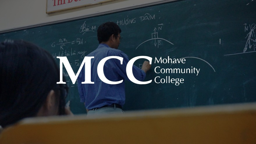 MCC logo with a teacher in the background writing on a chalk board teaching a class