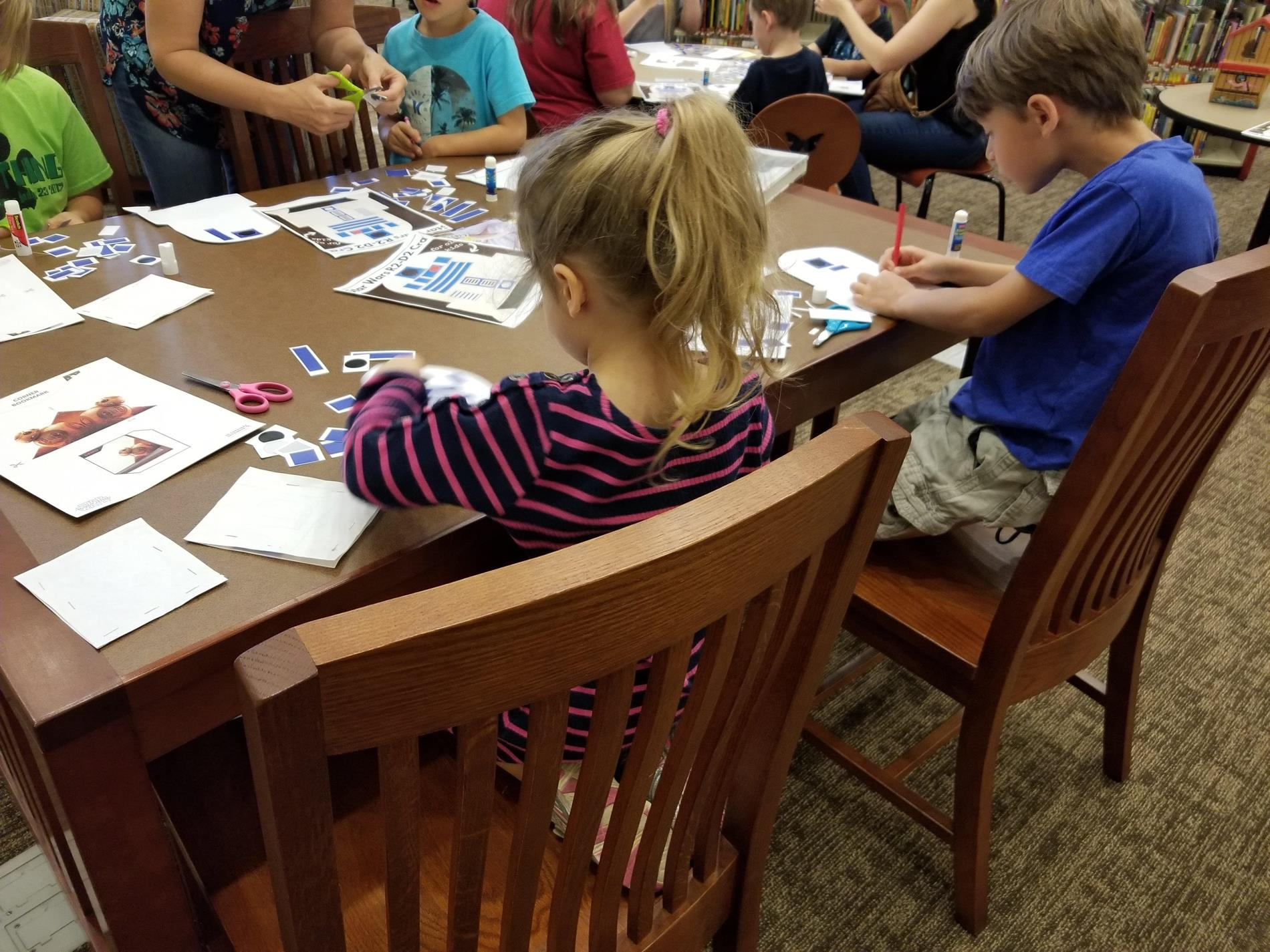 children at a table in the SFPL Library working on Star Wars themed crafts.