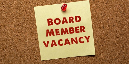 Corkboard with yellow sticky note that has Board Member Vacancy written in red ink