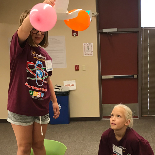 Girl dropping balloon during STEM academy experiment