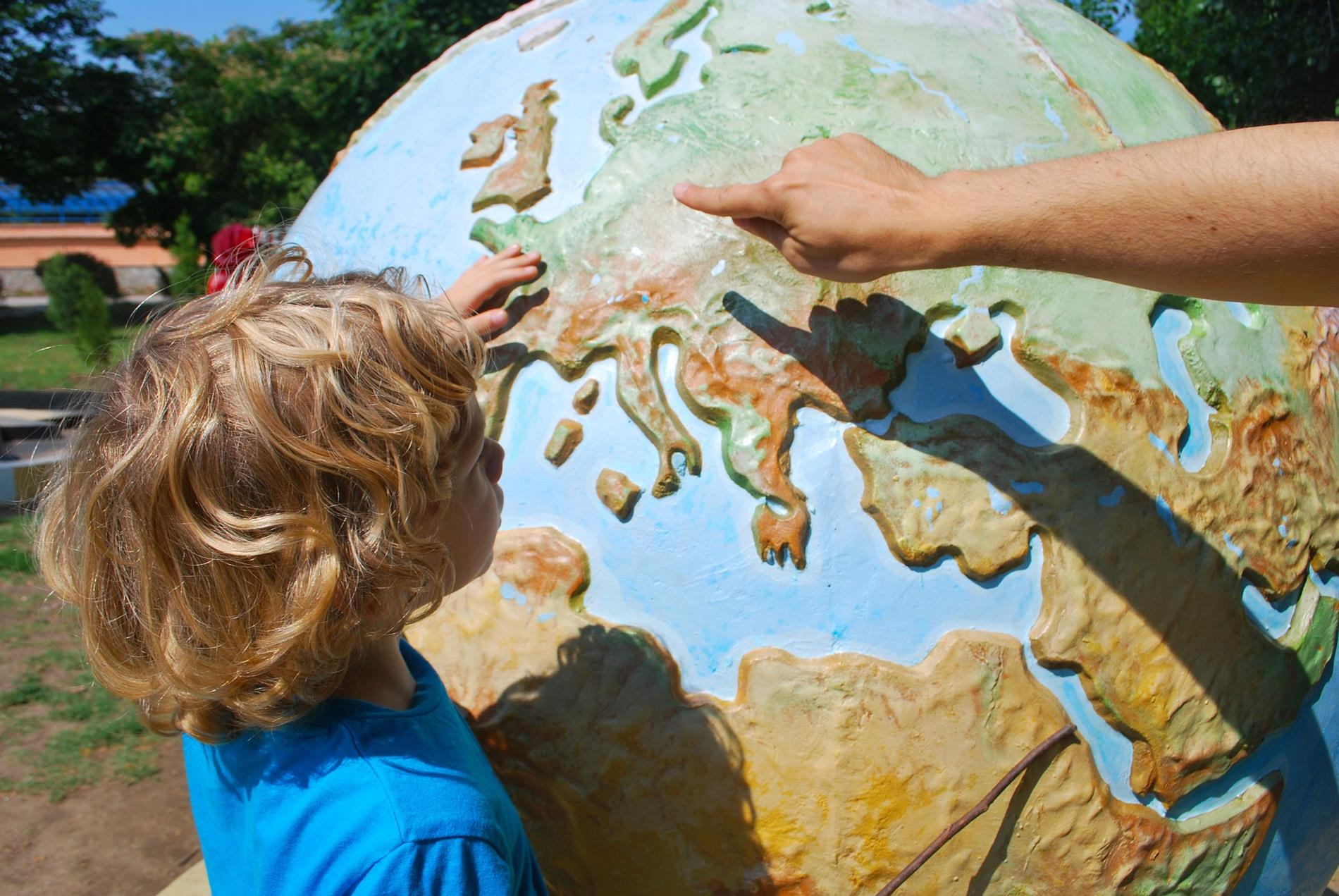 small child touching large globe with adult hand pointing finger at globe