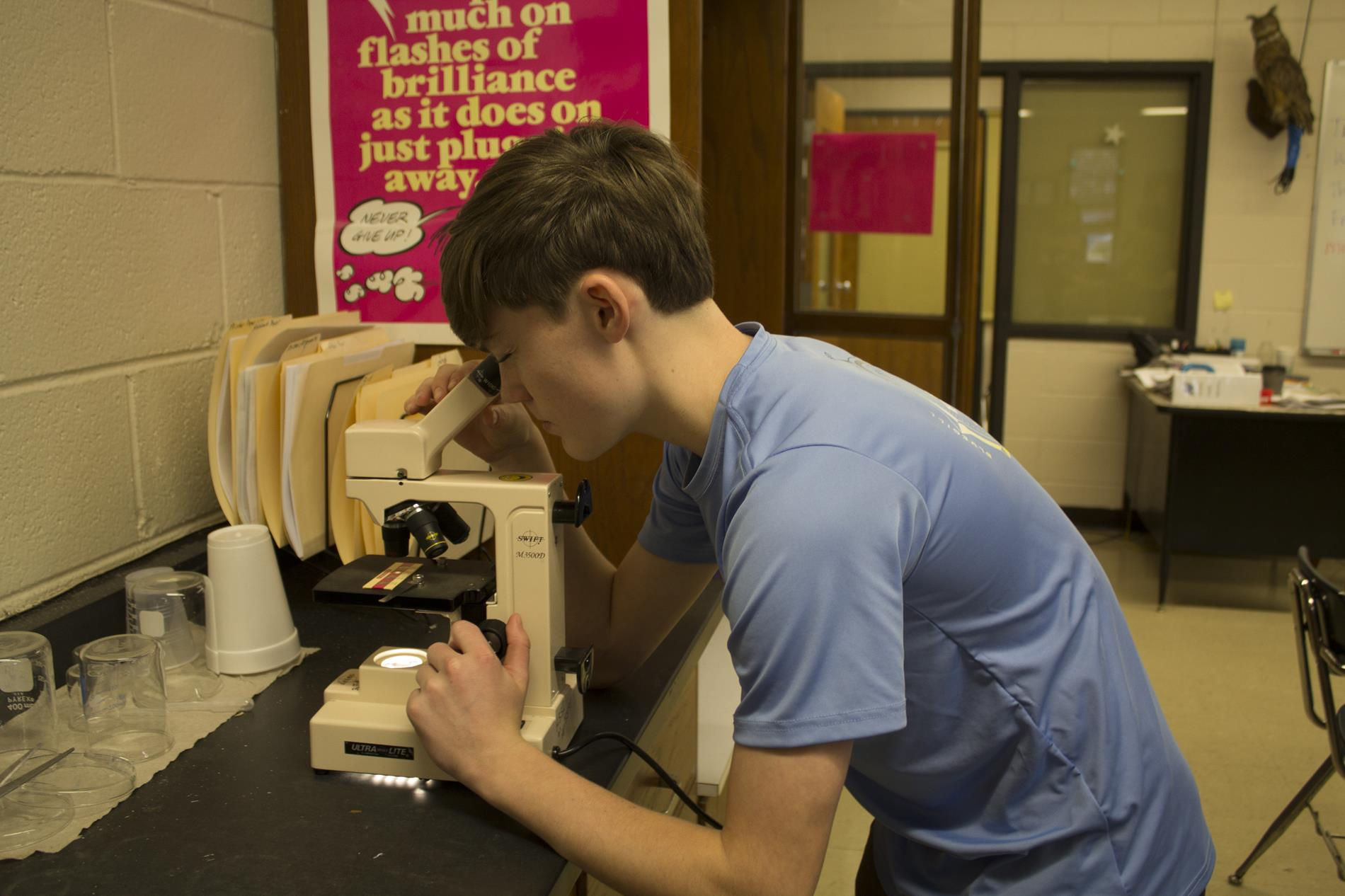 A student looks through a microscope in Biology class