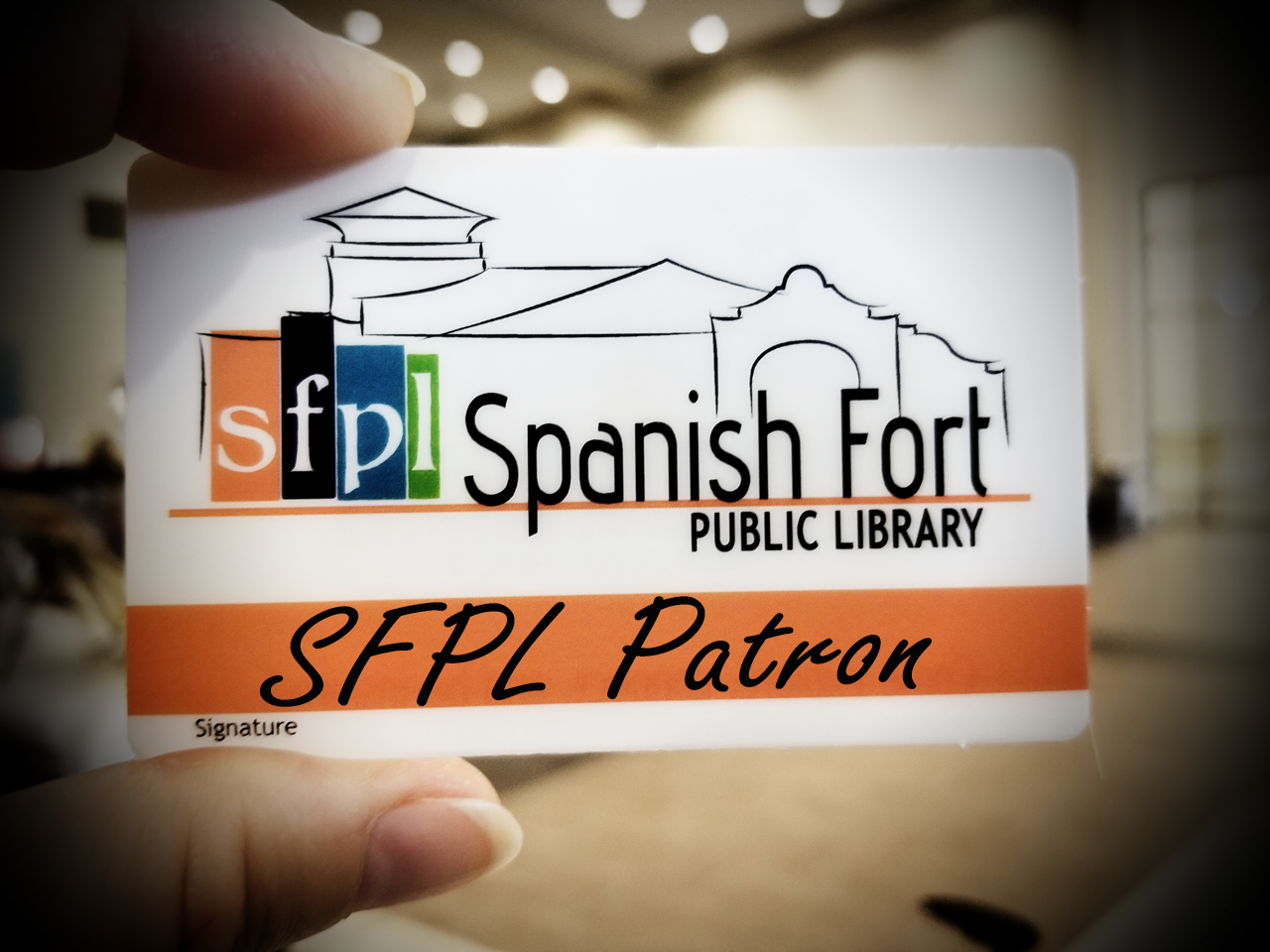 close-up photograph of a hand holding up a Spanish Fort Public Library patron card