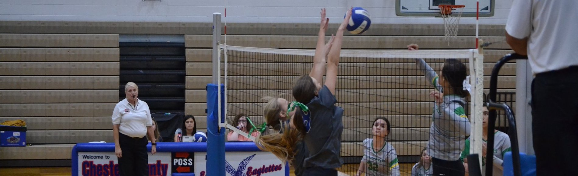 Volleyball players block at the net