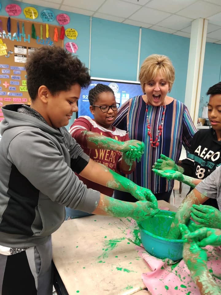 students and principal with a bowl of green slime