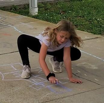 Girl drawing with chalk on sidewalk