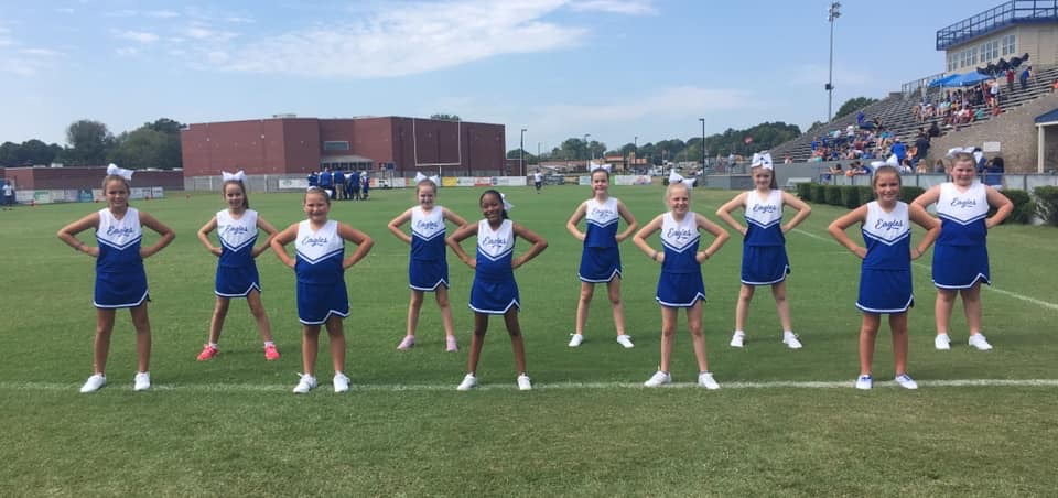 Cheerleaders stand at ready on the football field