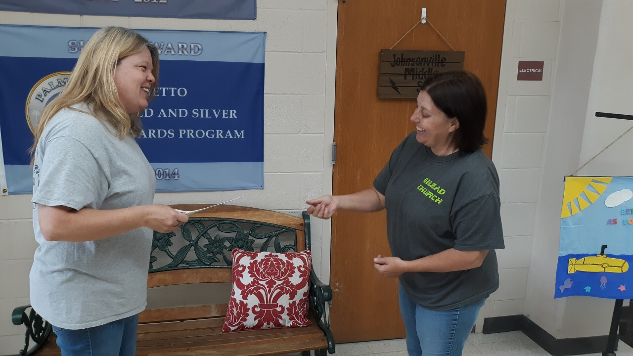 Ms. Smith giving Ms. Gamble the check