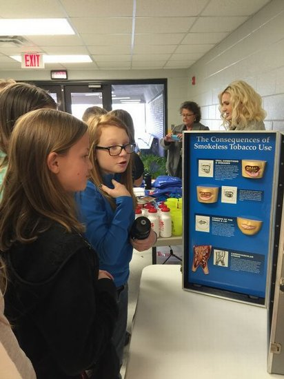DWS students looking at display of health effects of tobacco use.