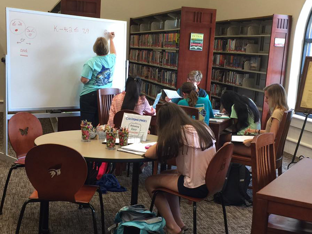 middle grade students at library tables participating in a study group with adult female tutor at whiteboard writing a math formula