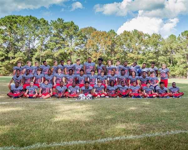 Football Middle School Team sitting on grass