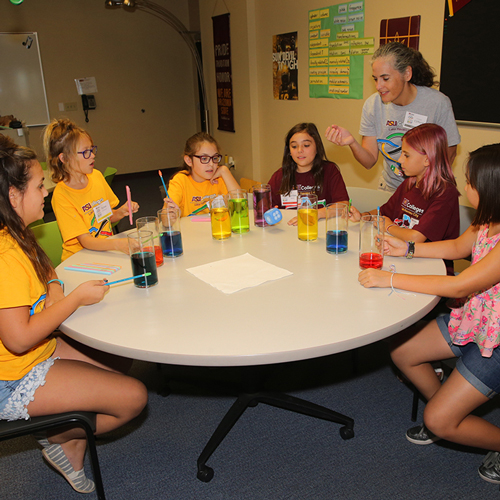 Girls work with colored water experiment during STEM academy