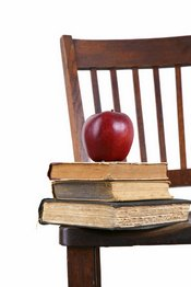 Apple and books stacked on top of chair
