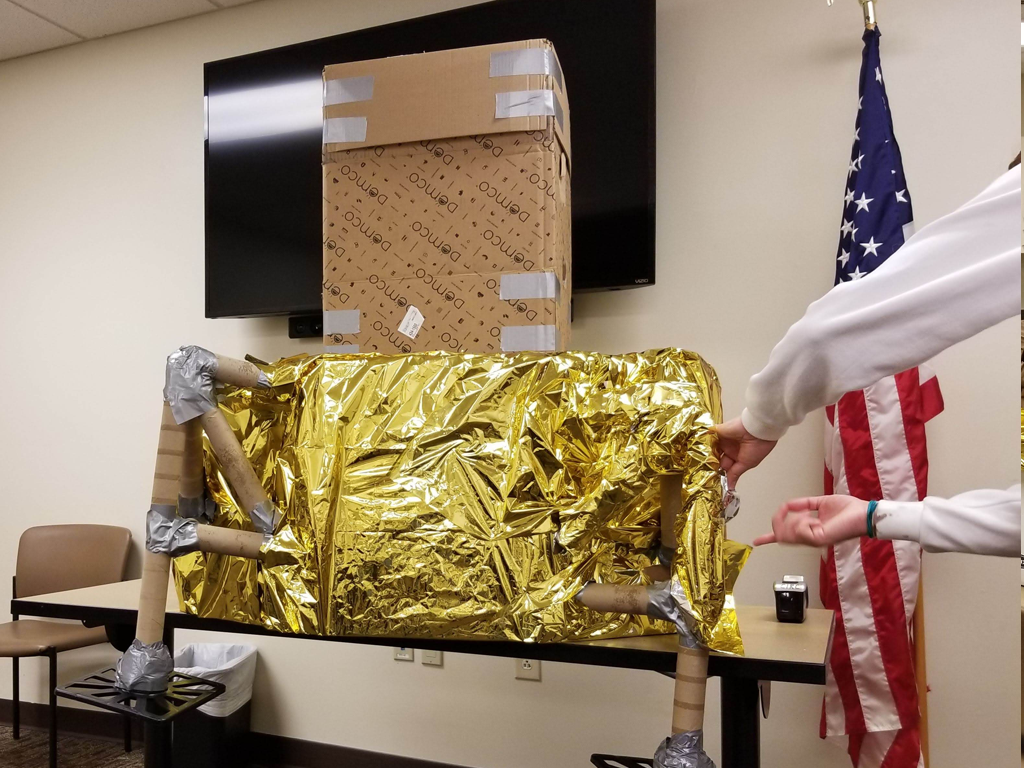 teen covering the base of the lunar module with mylar