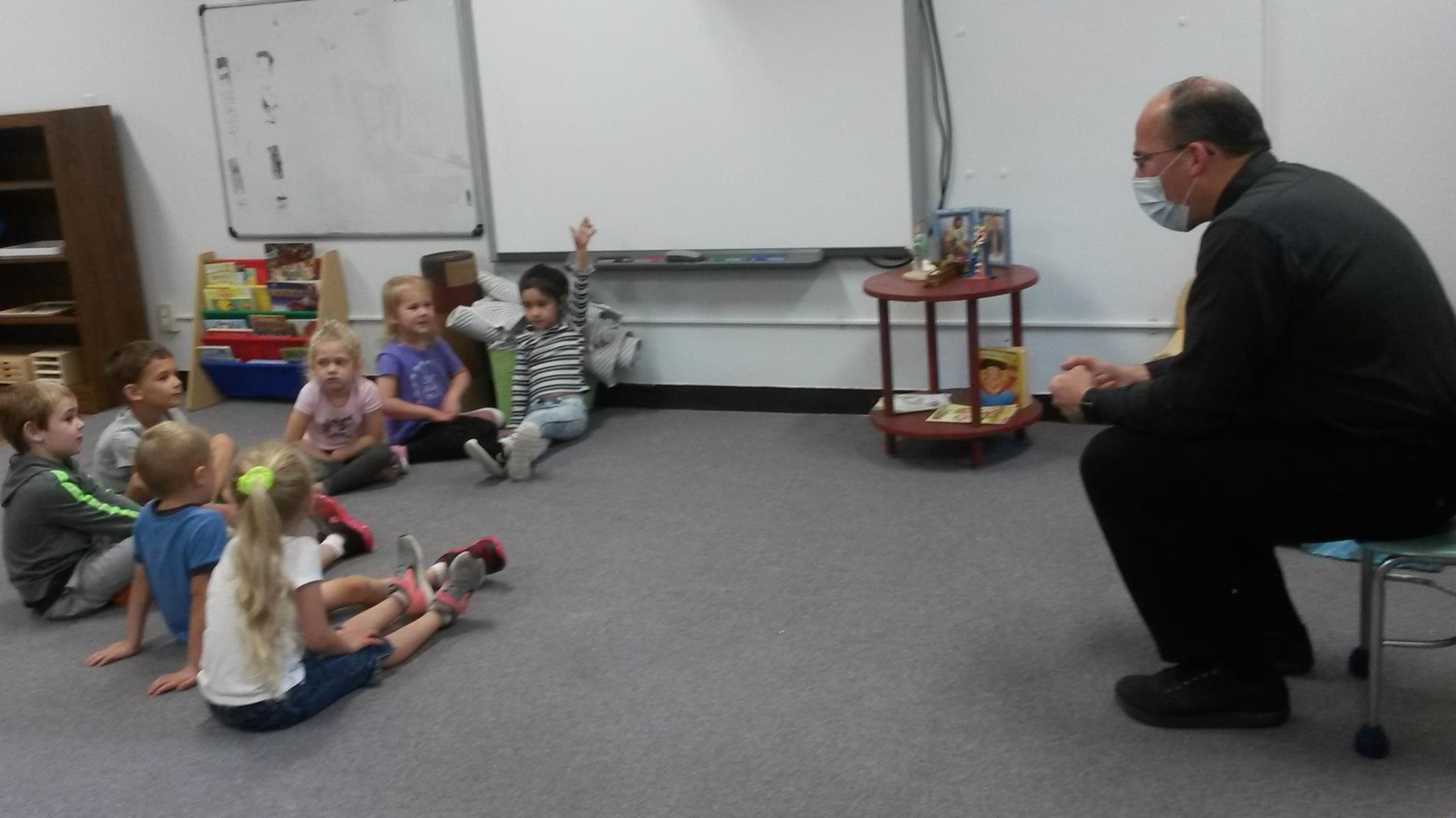 Priest teaching children