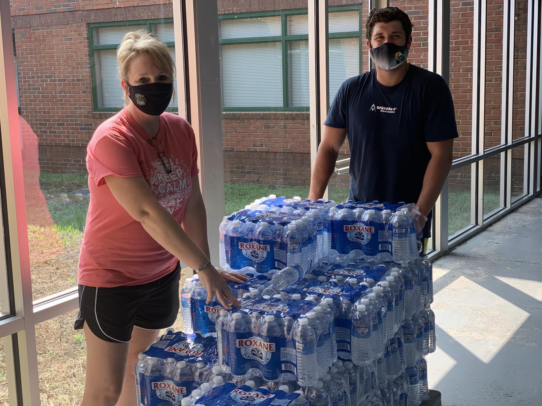 Mrs. Jarvis and Mr. Mosteller delivering water