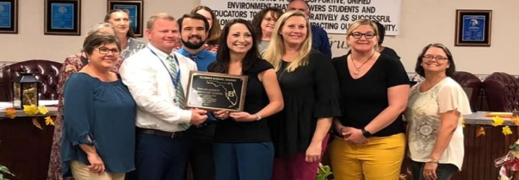 """Dr. Glover, school administrators and school teachers receive a plaque for being an """"A"""" School"""