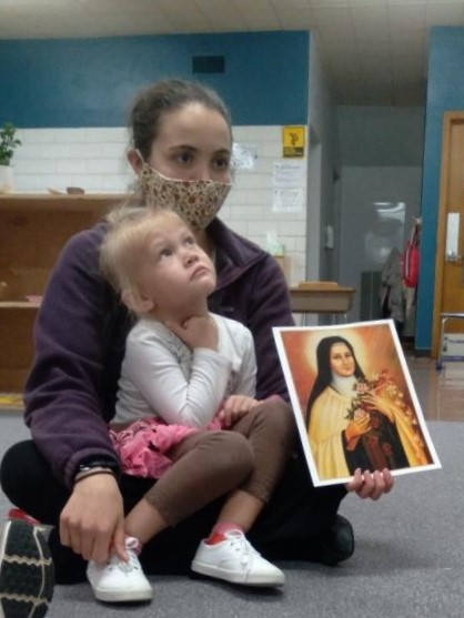 Teacher and child with a picture of a saint