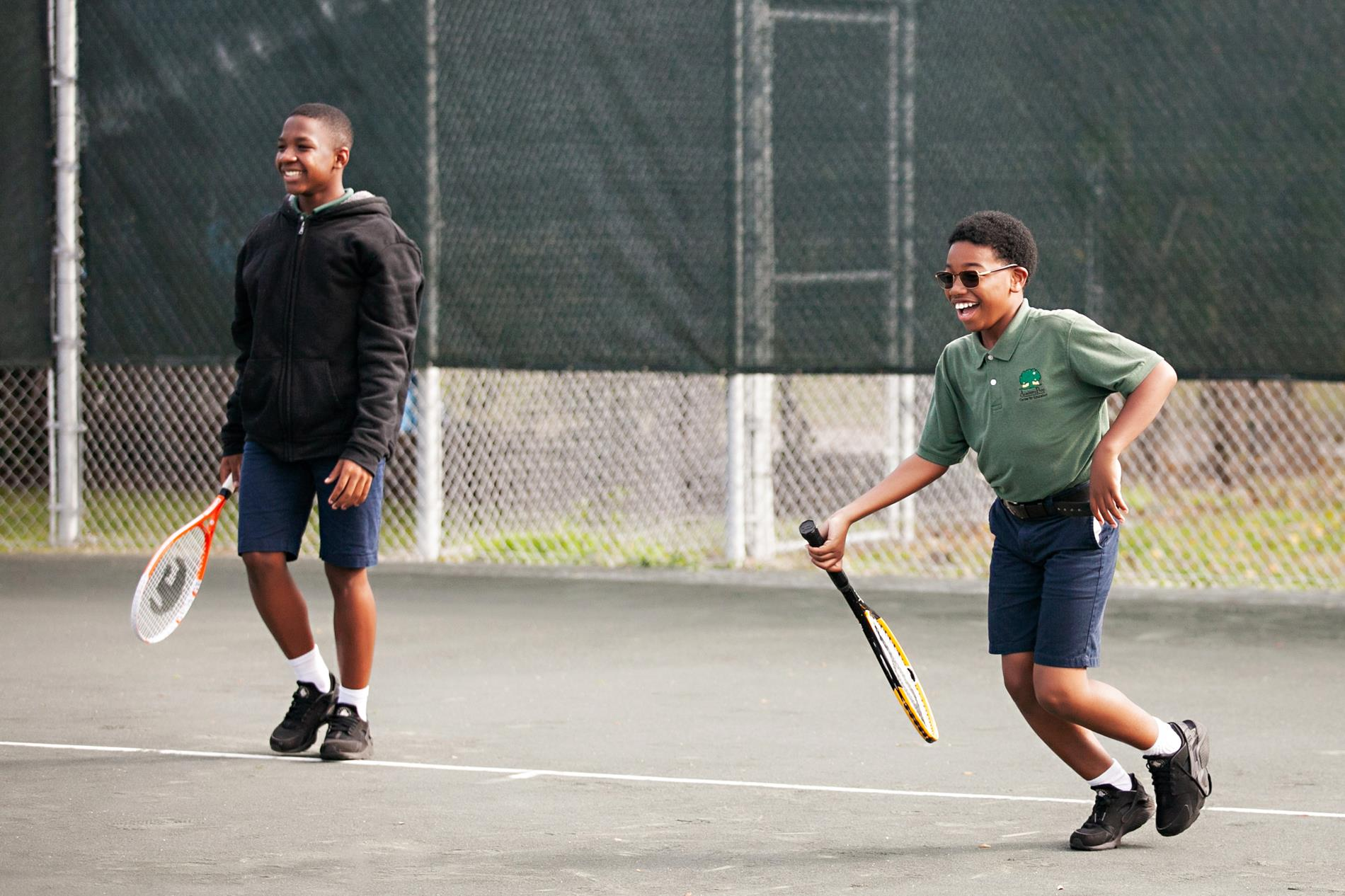 male students playing tennis