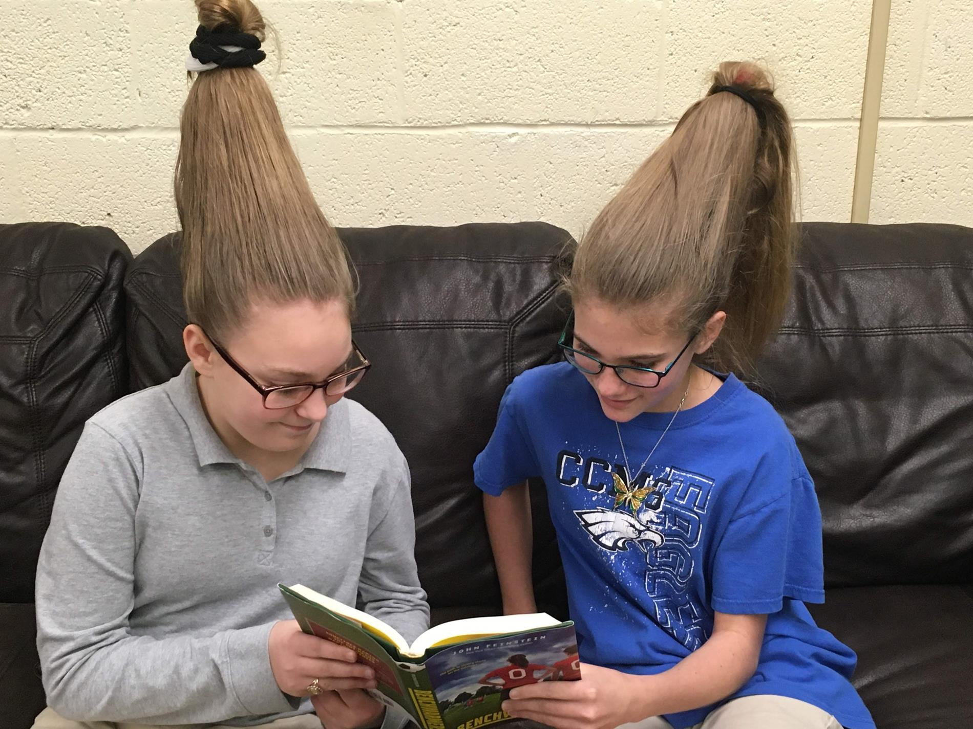 Students with hair standing up read a book together