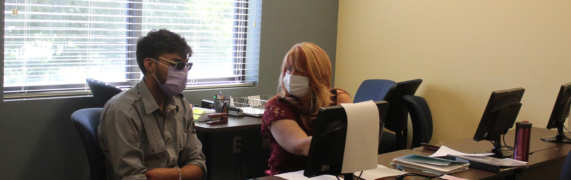 student and teacher working at computer wearing masks