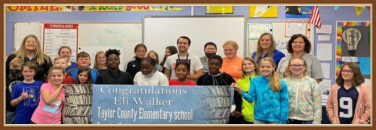 Mr. Eli Walker surrounded by students and administrators