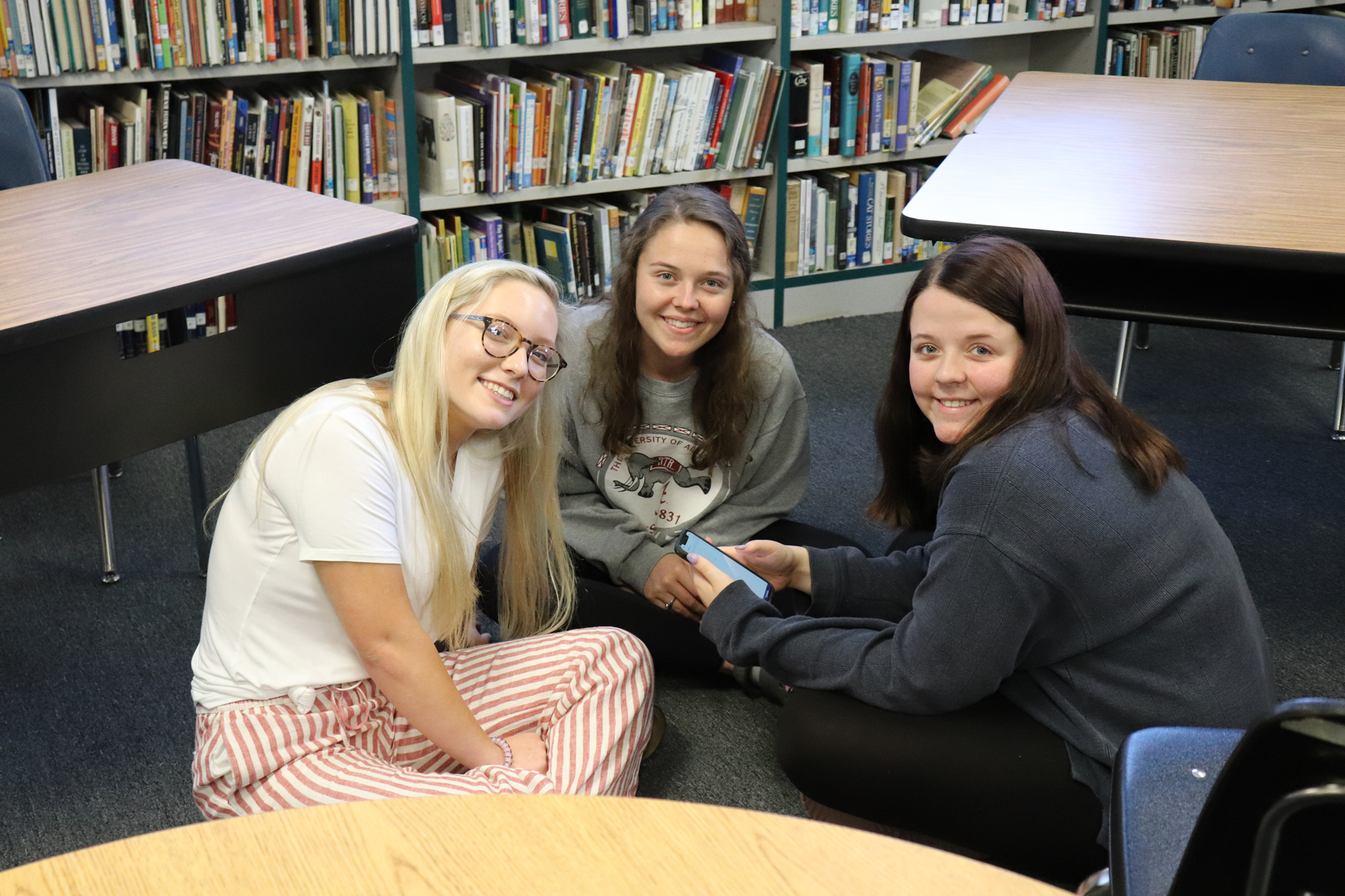 Gracey, Kayla, and Sara Beth are chilling in the library.