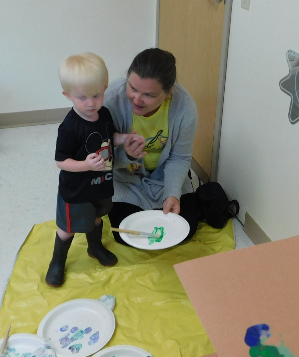 "Rome Family Partner, Carrie Spencer and ""child"" at the Athens Early Head Start playgroup, work to paint a section of the ""Hungry Caterpillar"" body."