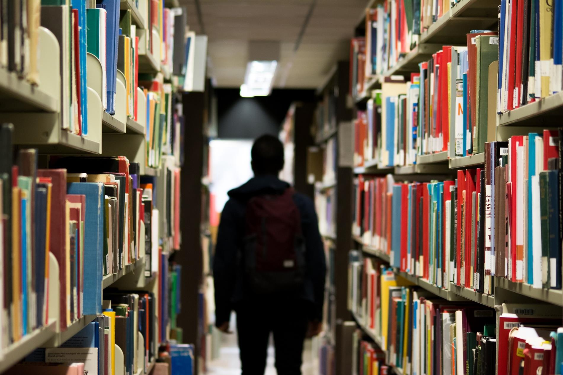 silhouette of a person walking away between shelves of books in a library