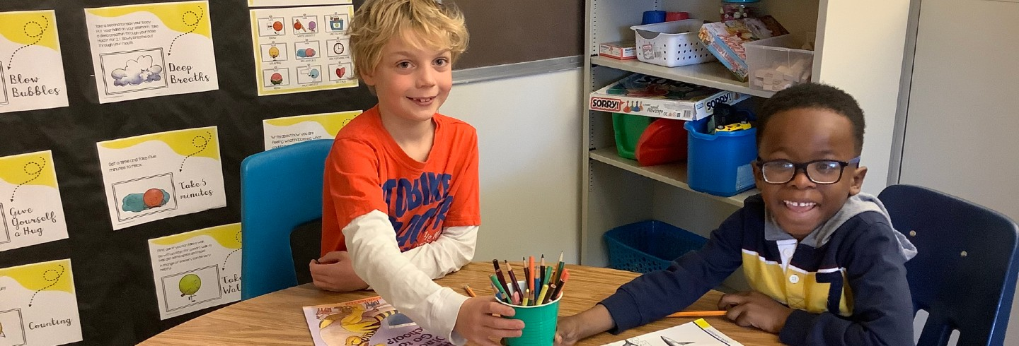 Two students sharing writing utensils