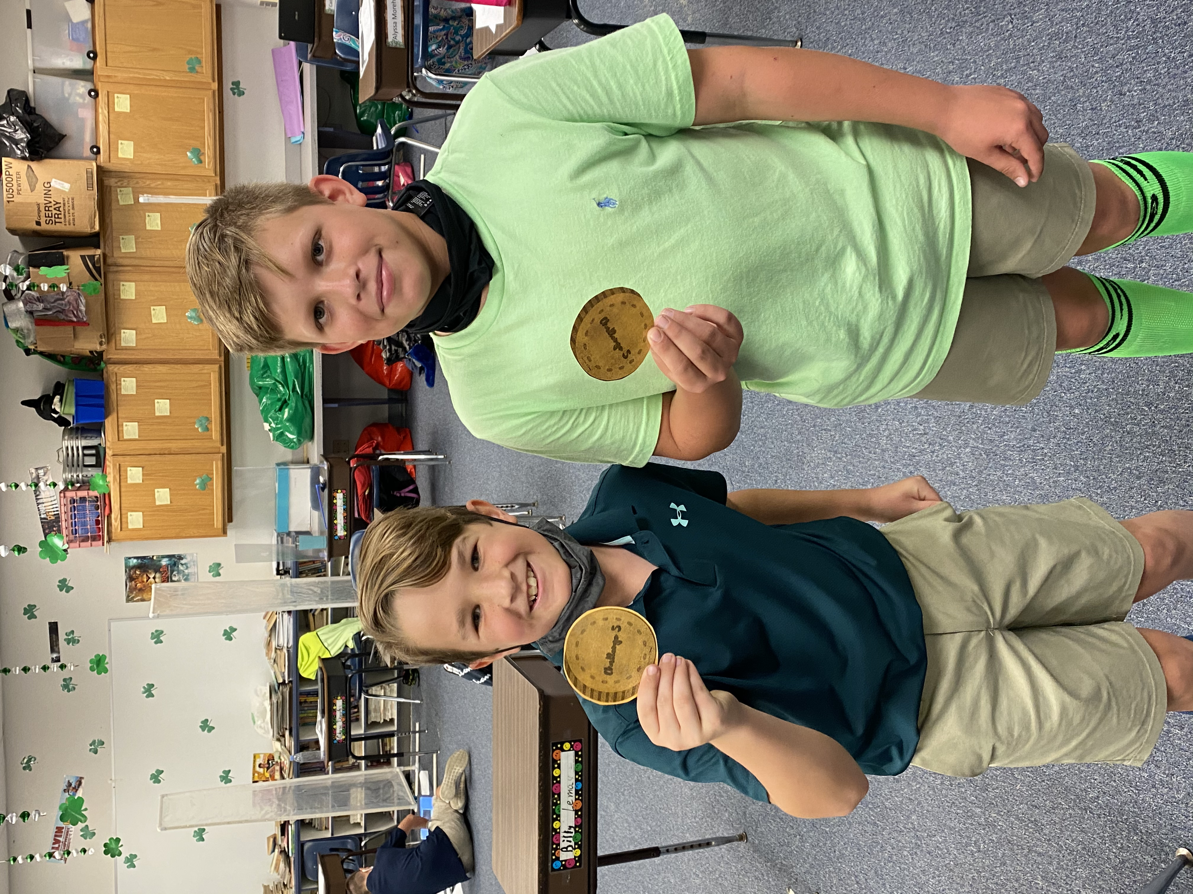 5th grade students showing the coins they earned.