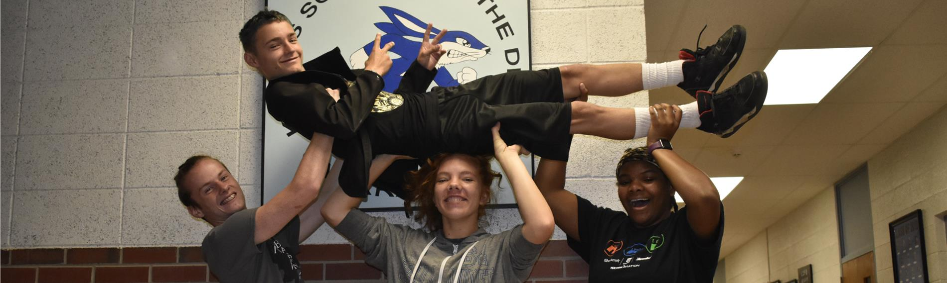 three students holding one student up in the air