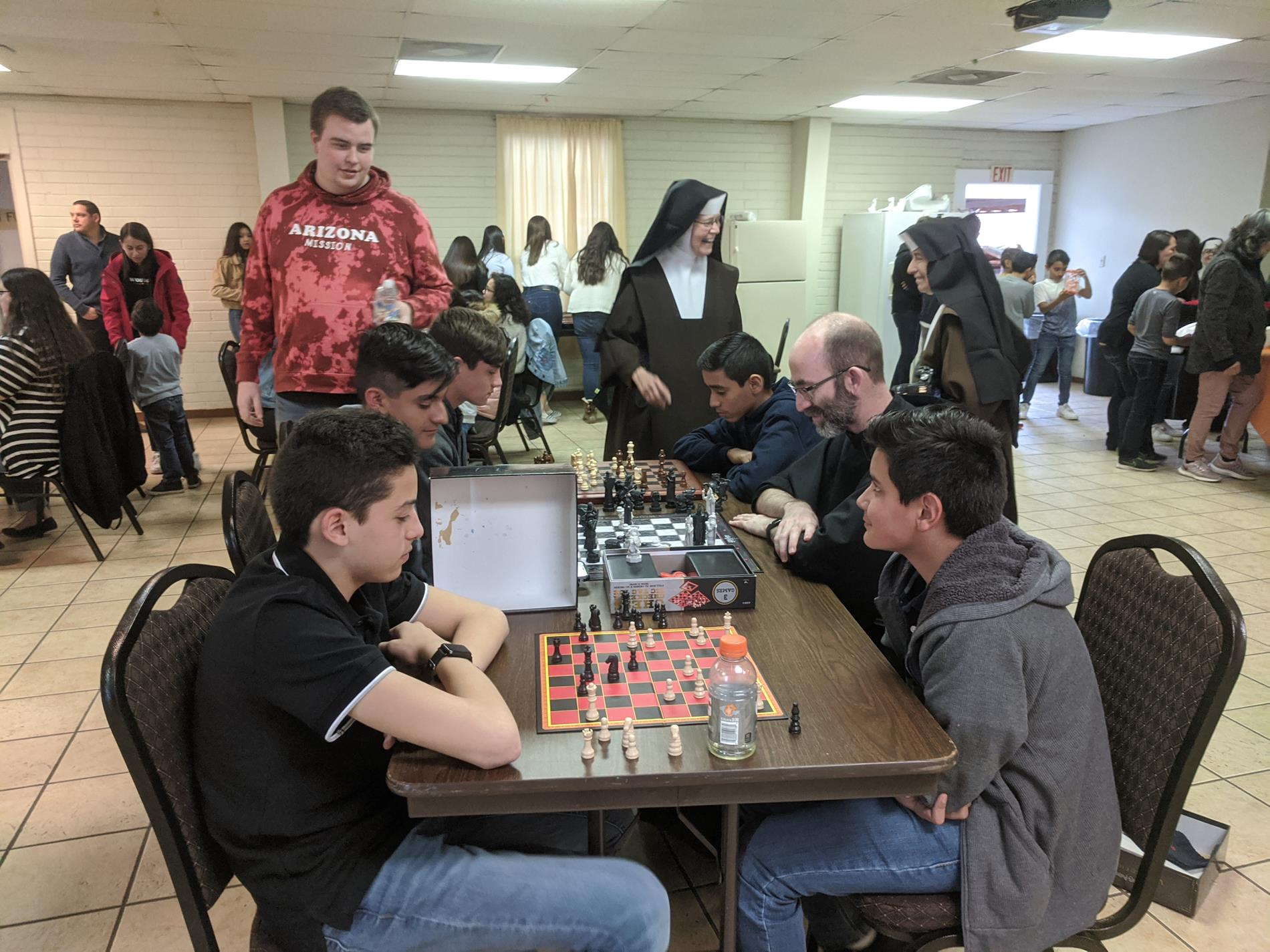 Students playing chess with a Franciscan friar who came from Franciscan University.