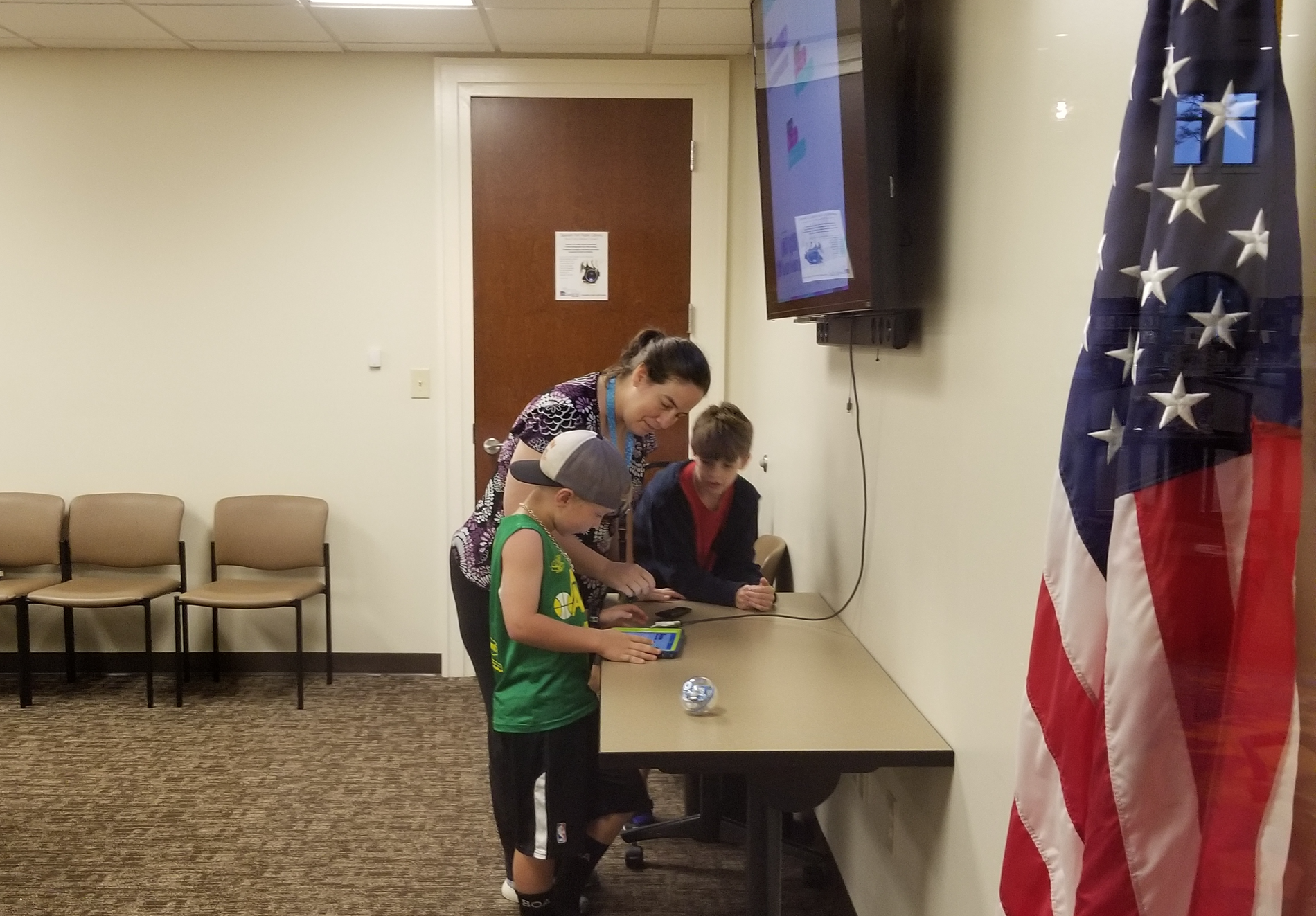 Children standing with SFPL staff member at table with coding robot and iPad