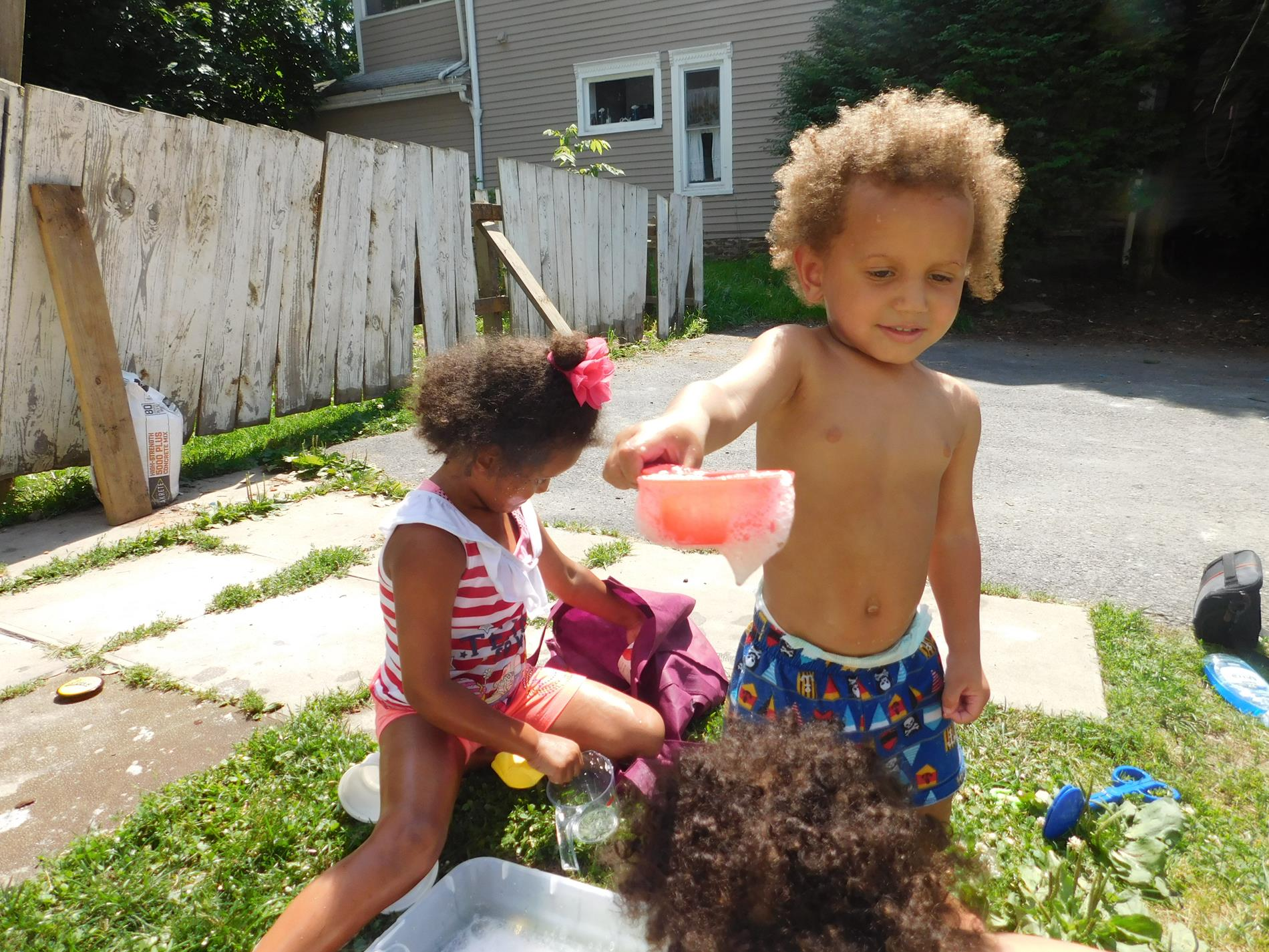 Canton Early Head Start child, Da'Kai uses a net to catch various toys hidden in the water and bubbles while playing with his sisters.
