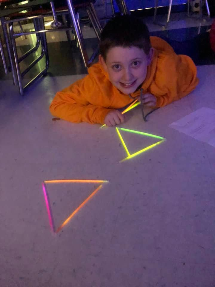student with glow sticks making shapes