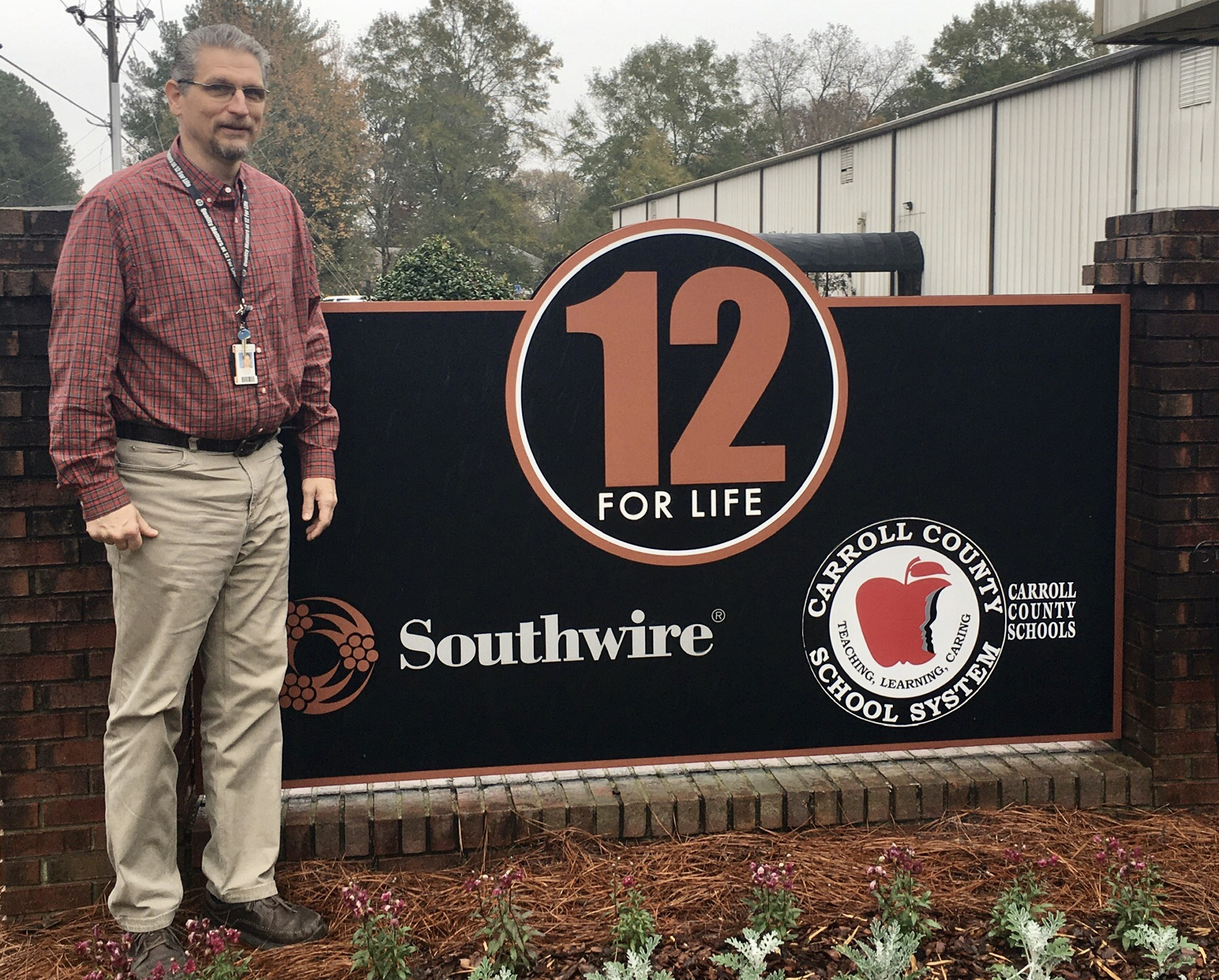 Joel Grubbs standing in front of the 12 for Life program sign outside the facility