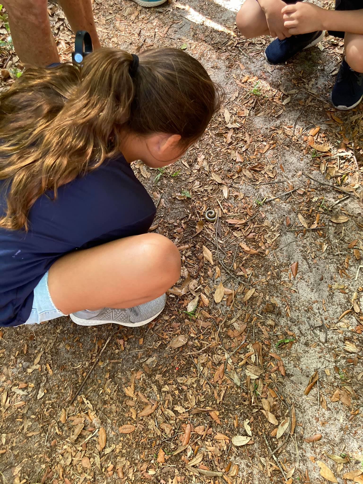 Students checking out a worm they found on one of the trails.